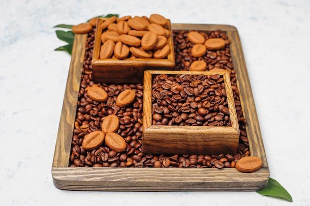 Composizione con chicchi di caffè tostati e chicchi di caffè a forma di biscotti sulla superficie della luce