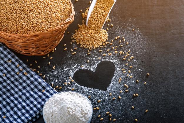 Composizione con chicchi di grano, farina con forma di cuore su sfondo nero