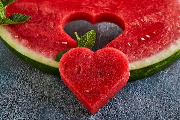 Composizione con cocomero maturo, foglie di menta e un cuore scolpito in una fetta di anguria. concetto per san valentino