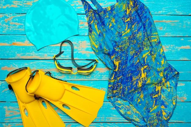 Composizione con costume da bagno su legno blu
