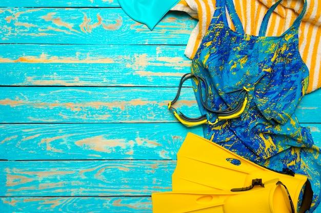 Composizione con costume da bagno sul colore di sfondo in legno