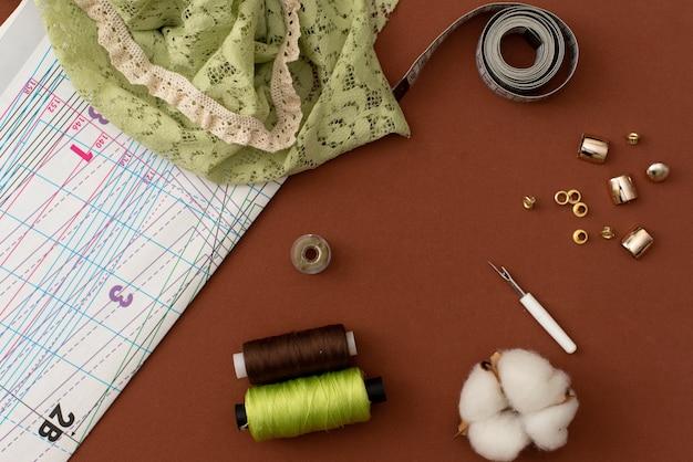 Composizione con filati cucirini e accessori su sfondo bianco, vista dall'alto