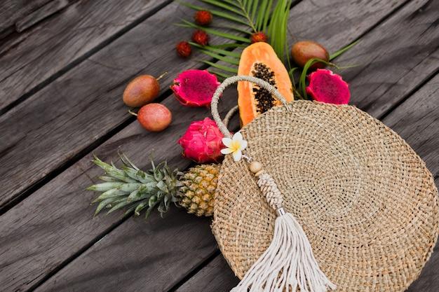 Composizione con frutti tropicali in sacchetto di paglia
