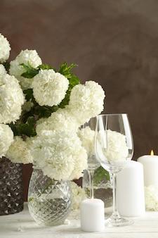 Composizione con i fiori e le candele dell'ortensia contro spazio marrone. serata romantica