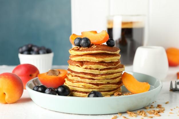 Composizione con i pancake e la frutta sulla tavola bianca. colazione dolce