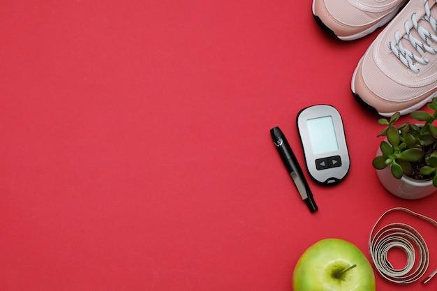 Composizione con il concetto di perdita di peso diabete dieta. scarpe da ginnastica, metro a nastro, glucometro su un rosso