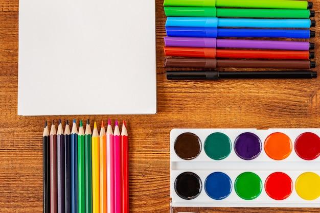 Composizione con il taccuino colorato della pagina in bianco della matita, indicatore e modello della penna di nuovo al concetto della scuola