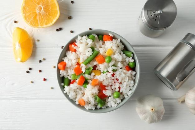 Composizione con la ciotola di riso delizioso sulla tavola di legno