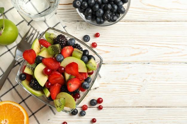 Composizione con la tazza di insalata di frutta fresca sulla tavola di legno bianca