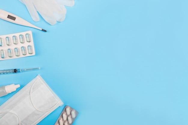Composizione con maschera medica, termometro, siringa, pillole e guanti su sfondo blu. copyspace.