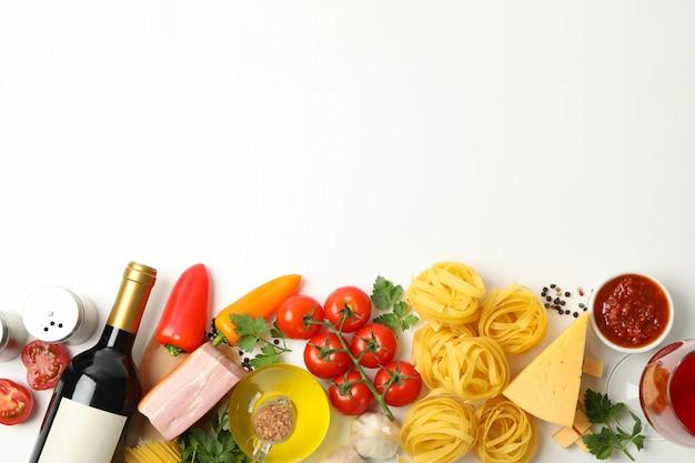 Composizione con pasta e ingredienti per la cottura sulla parete bianca, vista dall'alto