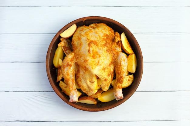 Composizione con pollo intero crudo con patate e spezie prima di cuocere su una teglia per un menu di ricette o design.