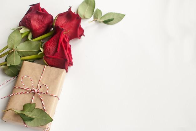 Composizione con regalo e bouquet di rose rosse su sfondo bianco