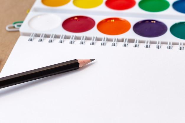 Composizione con taccuino pagina vuota matita colorata, pennarello e penna mock up torna al concetto di scuola con articoli di cancelleria per ufficio