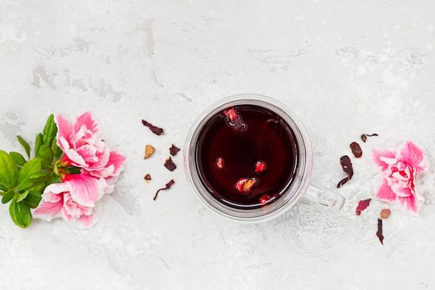 Composizione con tè di ibisco caldo in tazza di vetro con fiori rosa e foglie di tè secche. vista dall'alto.