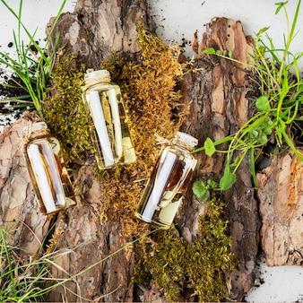 Composizione con tre bottiglie di vetro di cosmetici biologici per la cura del corpo con olio di frangipani, legno di sandalo, patchouli