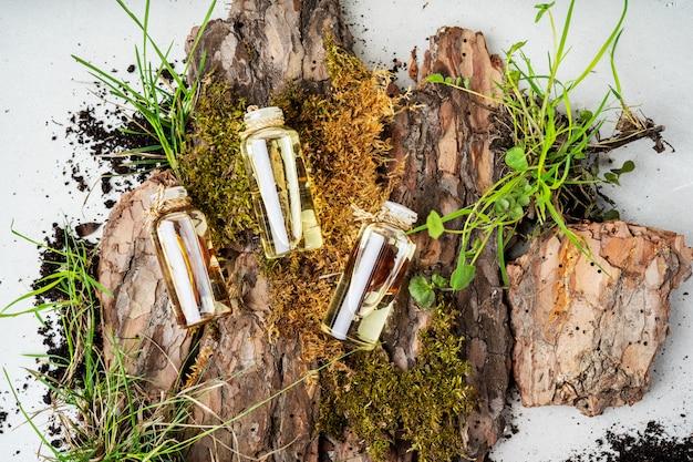 Composizione con tre bottiglie di vetro di cosmetici biologici per la cura del corpo con olio di frangipani, legno di sandalo