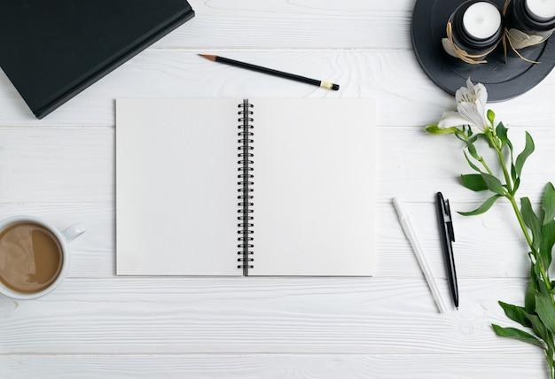Composizione con ufficio stazionario notebook penna matita caffè fiori piatto lay