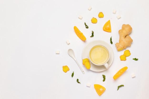 Composizione con una tazza di tè, arancia fresca, menta e zucchero