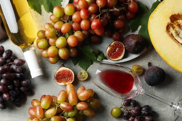 Composizione con uva, vino, fichi e melone su grigio