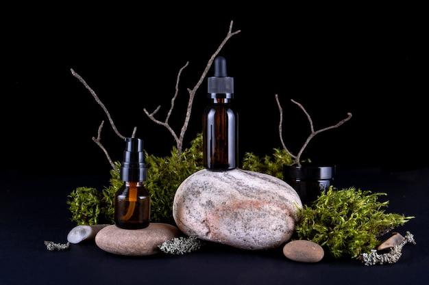 Composizione con varie bottiglie in vetro di cura del corpo su piedistallo in pietra con muschi