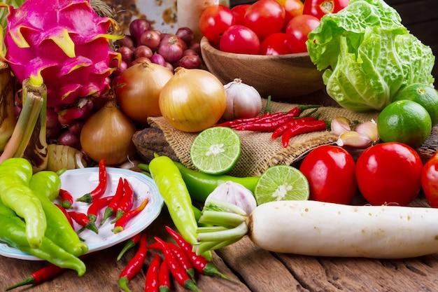 Composizione con verdure biologiche crude assortite sulla vecchia tavola di legno