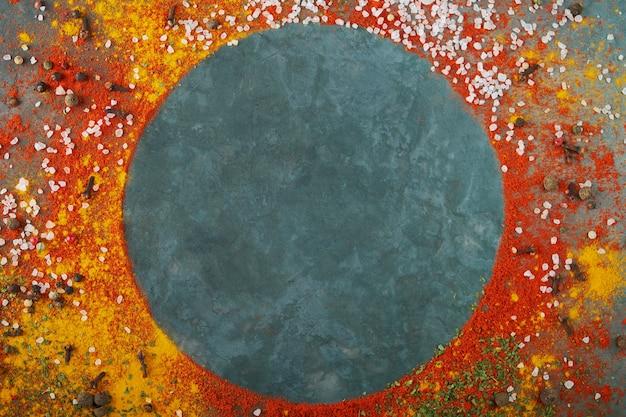 Composizione cornice rotonda, spezie diverse sparse sullo sfondo tavolo