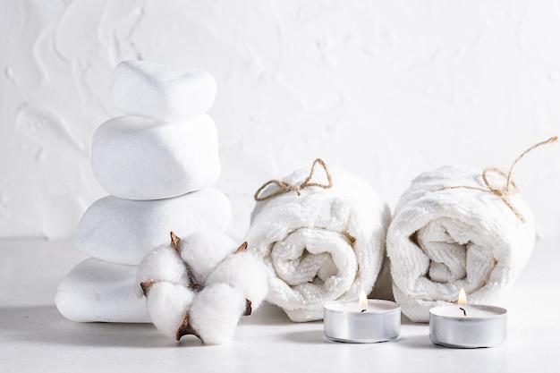 Composizione creativa con pietre zen, asciugamani arrotolati, candele e fiori di cotone su sfondo bianco.