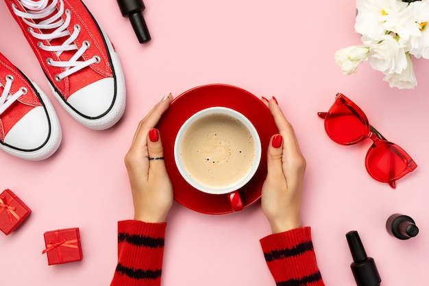 Composizione creativa con scarpe da ginnastica rosse, cosmetici e accessori su sfondo rosa. cartolina d'auguri di giorno di madri di giorno di compleanno della donna.