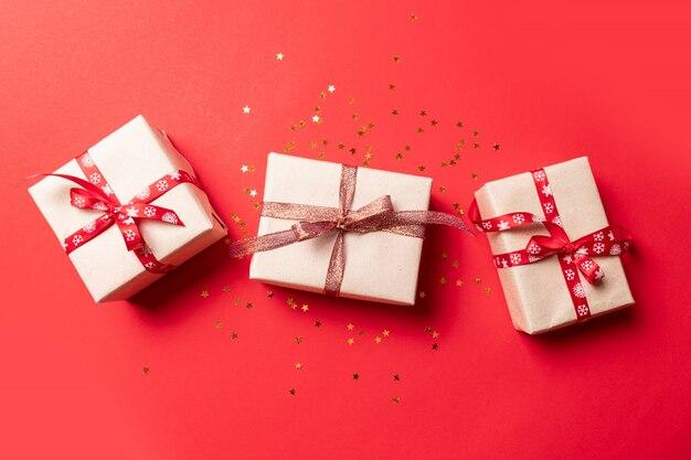 Composizione creativa con scatola regalo rosso, decorazioni vacanze nastri su rosso. composizione creativa per compleanno, natale, capodanno