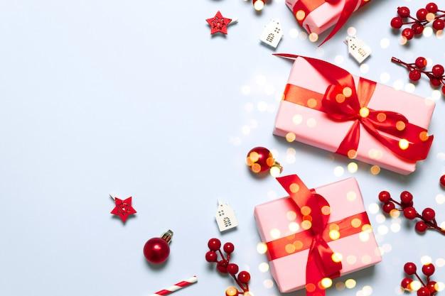 Composizione creativa con scatole rosa con nastri di raso rosso, rami di bacche e palle di natale