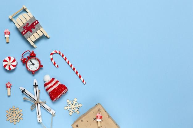 Composizione creativa natalizia ad angolo. bastoncino di zucchero, regalo in carta artigianale, slitta con cervi, cappello, sveglia, sci, mollette, fiocchi di neve in legno su blu