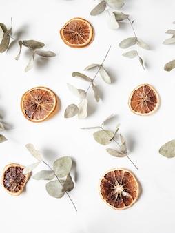 Composizione creativa naturale di rami secchi di eucalipto e fette secche di arancia