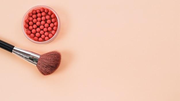 Composizione dalla spazzola di trucco e rouge su sfondo chiaro