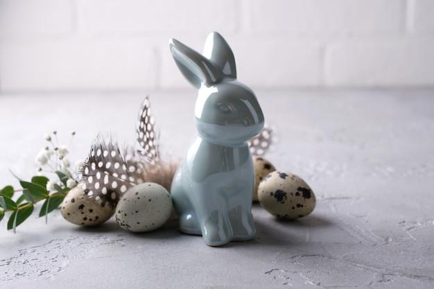 Composizione decorativa in primavera di pasqua con uova di quaglia di pasqua e rametti di foglie di eucalipto e coniglio in ceramica con posto per il testo.