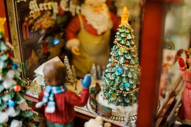 Composizione decorativa nel giocattolo di natale che consiste in un ragazzo che osserva attraverso la finestra