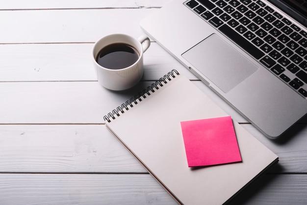 Composizione del blocco note e del computer portatile sullo scrittorio