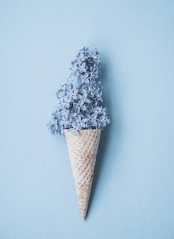 Composizione del cono gelato con fiori lilla viola. flat lay. vista dall'alto. concetto di estate creativa