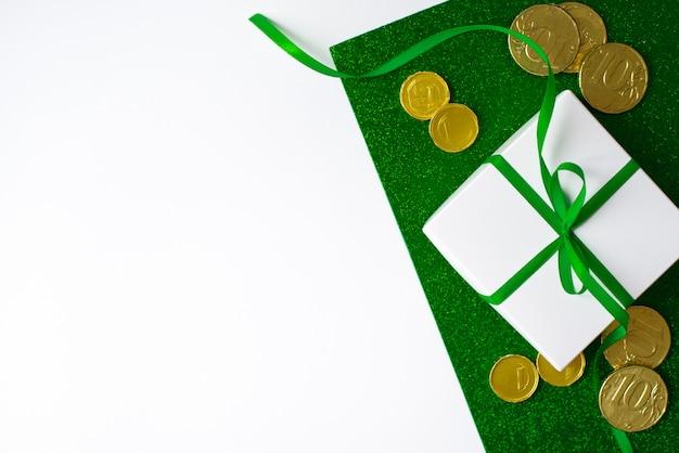 Composizione del giorno di san patrizio. contenitore di regalo bianco con fiocco verde e monete d'oro su uno sfondo verde lucido e bianco