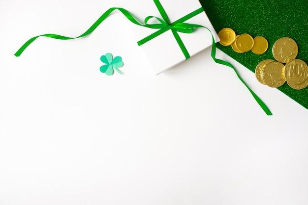 Composizione del giorno di san patrizio. scatola regalo bianca con un fiocco verde, un pezzo di carta di trifoglio e monete d'oro su uno sfondo verde lucido e bianco