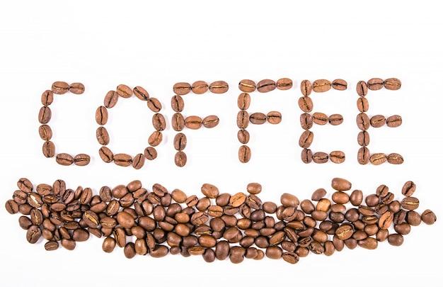 Composizione del primo piano arrostito dei chicchi di caffè su un fondo bianco