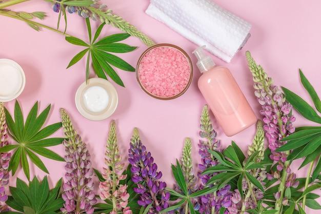 Composizione del prodotto della stazione termale con i fiori, l'asciugamano e il cosmetico del lupino su un rosa