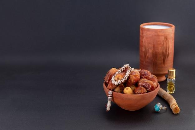 Composizione del ramadan con datteri, disordine, perle di preghiera, itar e latte in contenitori di ceramica