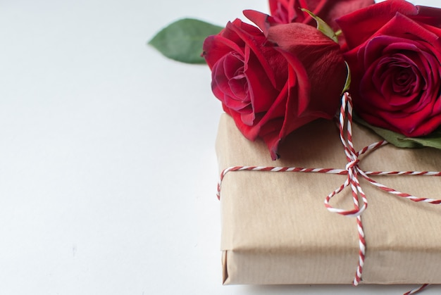 Composizione del regalo e mazzo delle rose rosse su fondo bianco