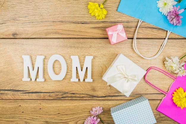 Composizione del titolo della mamma vicino a fiori freschi, scatole presenti e pacchetti di carta