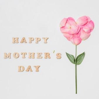 Composizione del titolo di giorno di madri felice vicino alla fioritura rosa a forma di cuore