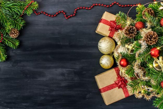 Composizione della tavola di natale per i messaggi delle vacanze invernali. albero di natale, regali, pigne, palle di natale, luci di natale e stelle su un bel legno scuro.