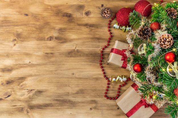 Composizione della tavola di natale per i messaggi delle vacanze invernali. albero di natale, regali, pigne, palle di natale, luci natalizie e stelle su un bel legno marrone.