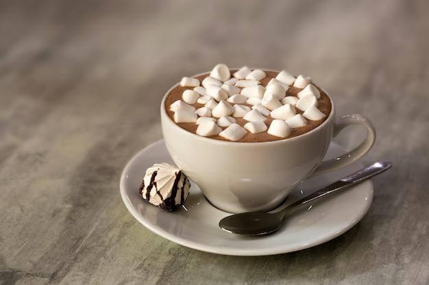 Composizione della tazza di caffè con caramelle gommosa e molle sul piatto di porcellana su sfondo chiaro, vista dall'alto.