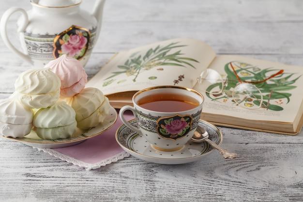 Composizione della tazza di tè e del libro aperto sul tavolino da salotto nella stanza, fine su